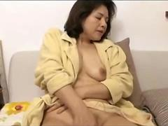 Mature woman in bathrobe masturbating her pussy with toys