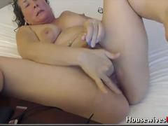 A horny housewife teasing naked and masturbating alone on a bed on the webcam
